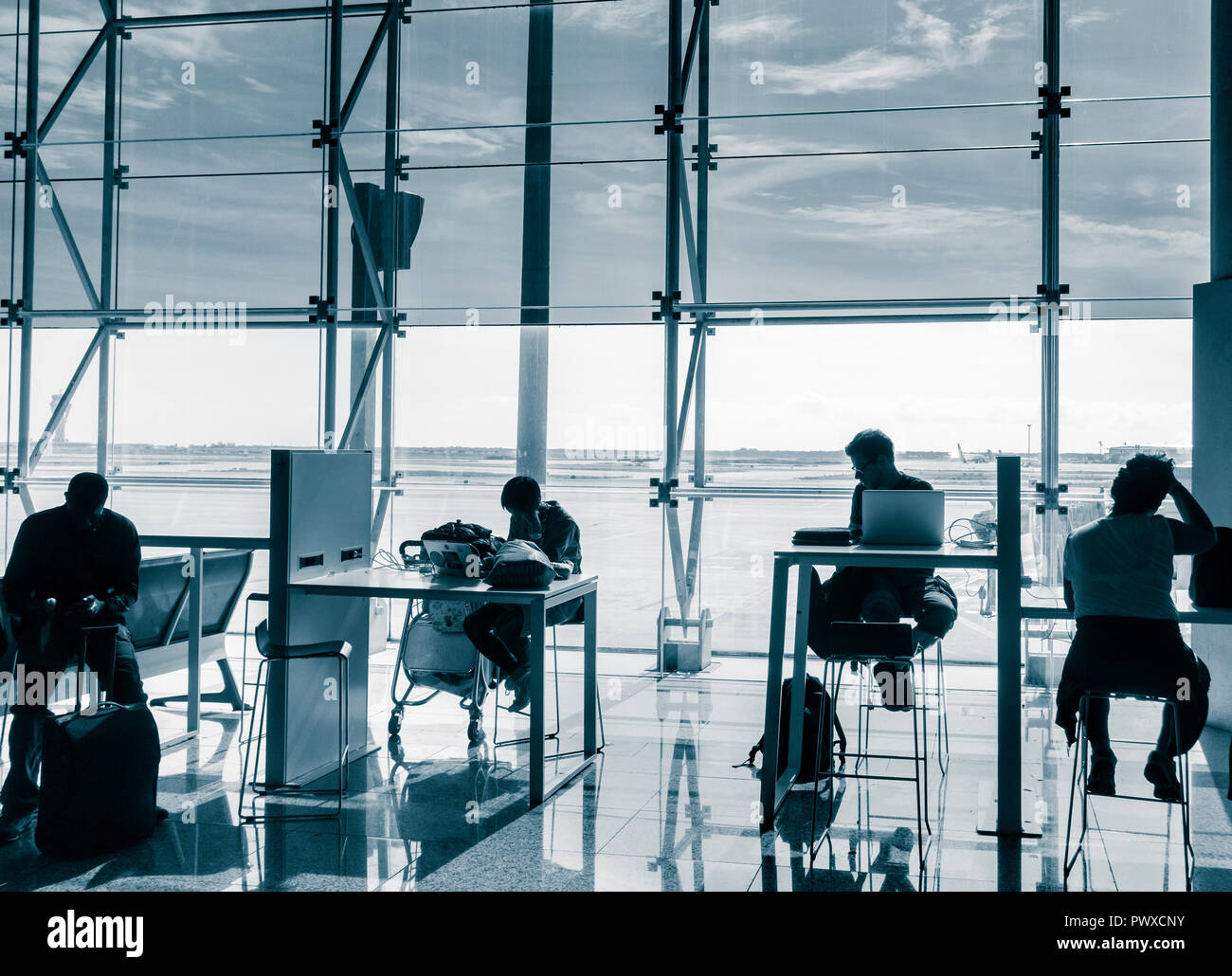People using mobile devices and laptops in Wifi zone at Barcelona El Prat airport. Spain - Stock Image