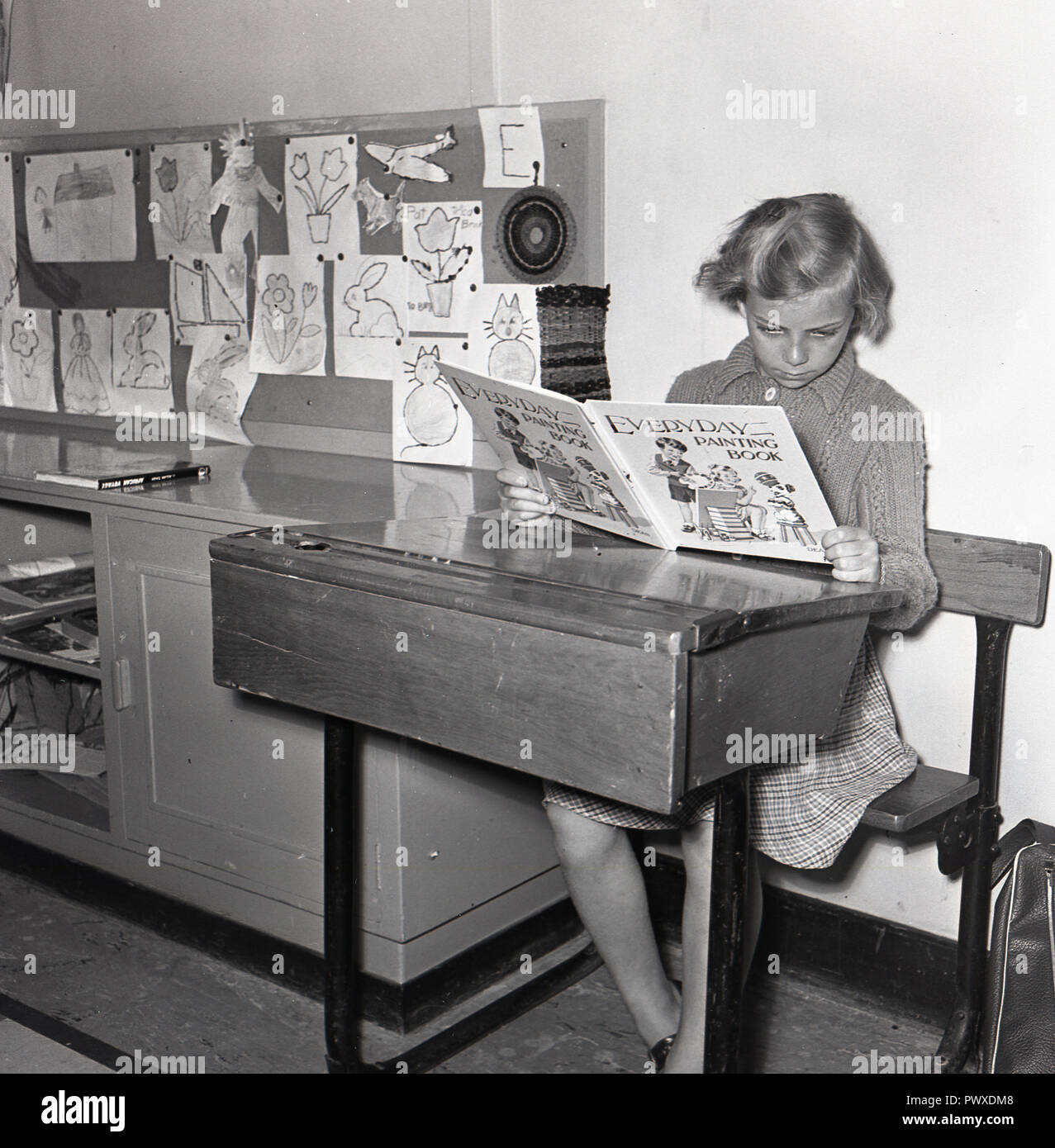 1950s, historical, young girl in a nursery or playgroup sitting at a small wooden and metal framed school desk - with inkwell and lift up lid -  looking at an Everyday painting book, England, UK. - Stock Image