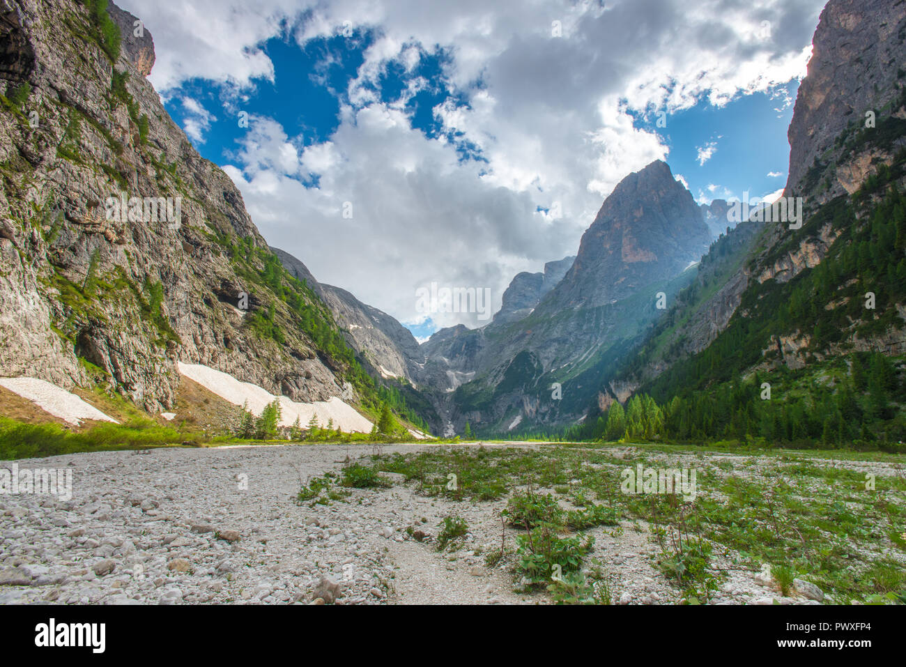 Fantastic scene of sunlight filtering from the rocky peaks down to the valley bottom. Hiking in the wild, solitude, unspoiled mountain destination. Stock Photo