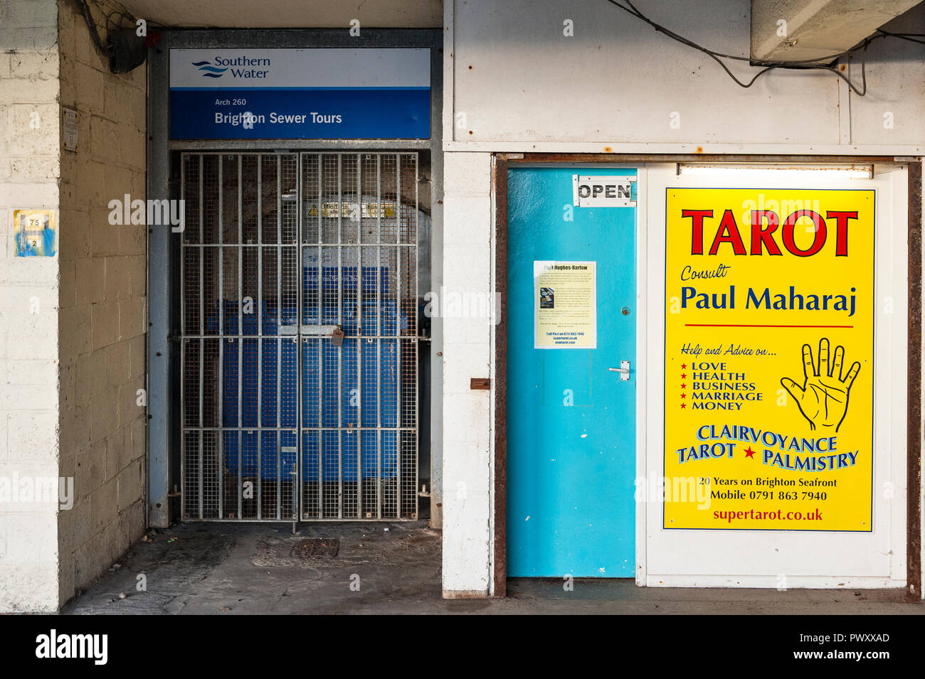 Brighton, East Sussex, UK. The entrance for tours of the town sewers, next to a poster advertising tarot readings and clairvoyancy - Stock Image