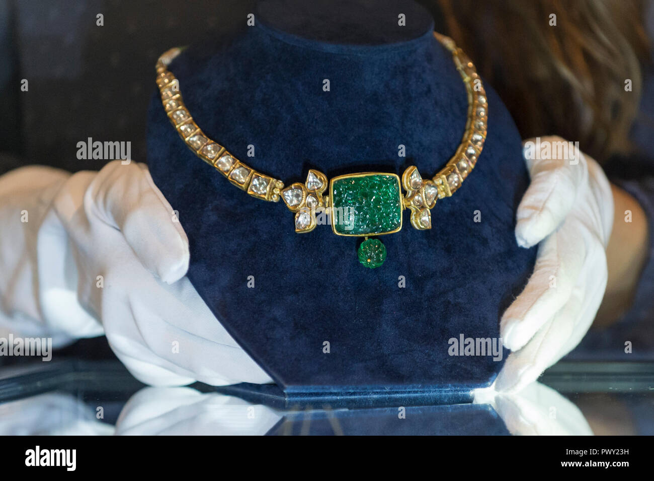 London, UK.  18 October 2018.  A staff member presents 'An emerald and diamond-set necklace', India, late 19th century (Est. GBP15,000 to 20,000). Preview of Bonhams Asian Art Week which features works to be offered in the Islamic and Indian, Modern and Contemporary Middle Eastern art sale on 23 October and Modern and Contemporary South Asian art sale on 24 October.   Credit: Stephen Chung / Alamy Live News - Stock Image