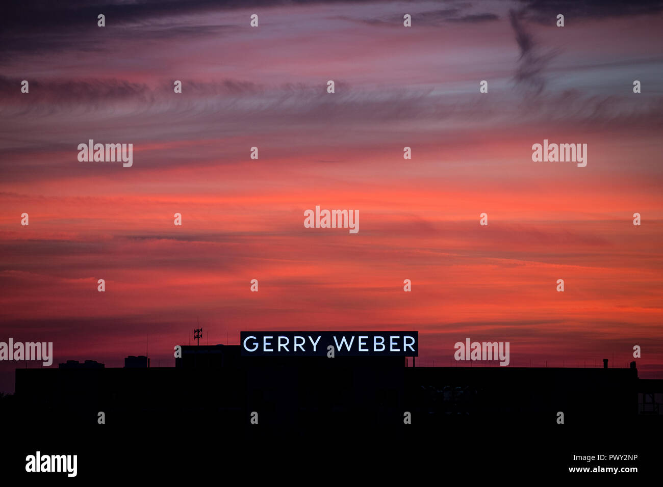 Halle, Germany. 17th Oct, 2018. The emblem of the fashion company Gerry Weber shines in front of the red sky at dusk. The Westphalian textile company continues to struggle with declining sales and expects to be in the red again this year. Credit: Friso Gentsch/dpa/Alamy Live News Stock Photo