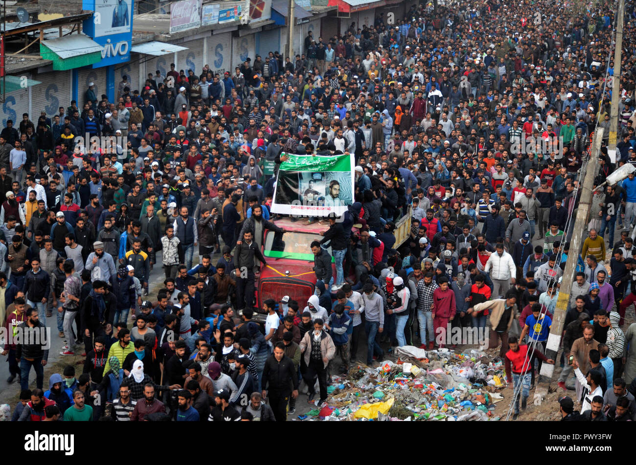 October 17, 2018 - A large crowd carry the body of Mehraj Bangroo, a rebel commander killed during a gun fight with Indian government forces at Fateh Kadal in Srinagar on 17 October 2018. According to police sources, an early morning cordon and search operation turned into a gun battle during which Lashkar-e-Toiba top commander, Mehraj Bangroo, and his associate Fahad Waza were killed. The police issued a statement saying that one policeman was also killed and three were injured in the encounter and that Raees Ahmed, the owner of the house where the militants were hiding, was also killed (Cre - Stock Image