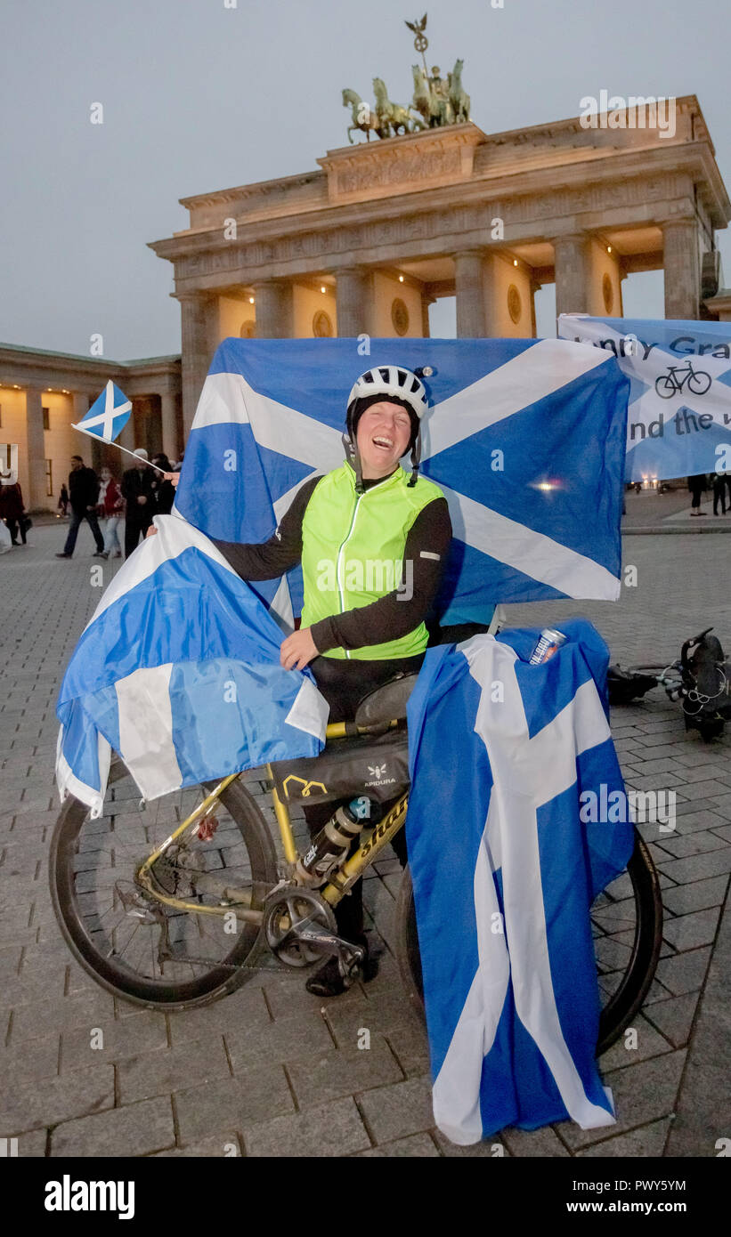 Berlin, Germany. 18th Oct, 2018. Jenny Graham laughs when she arrives at the Brandenburg Gate after having circumnavigated the world by bicycle. They have Scottish flags hanging from their bicycles. The British woman was the first woman to circumnavigate the world by bicycle alone in only 125 days. The previous world record was 144 days. Credit: Christoph Soeder/dpa/Alamy Live News - Stock Image