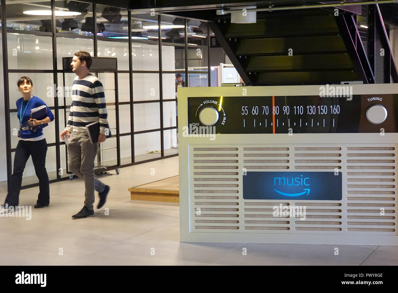 "London, UK. 18th Oct, 2018. Amazon employees walk past an oversized radio model in London's Amazon headquarters that promotes the Amazon Music streaming service. At its ""Innovation Day"", the Group announced that it would expand its development locations in Europe. (Zu dpa ""Amazon is expanding research and development centers in Europe"") Credit: Christoph Dernbach/dpa/Alamy Live News Stock Photo"