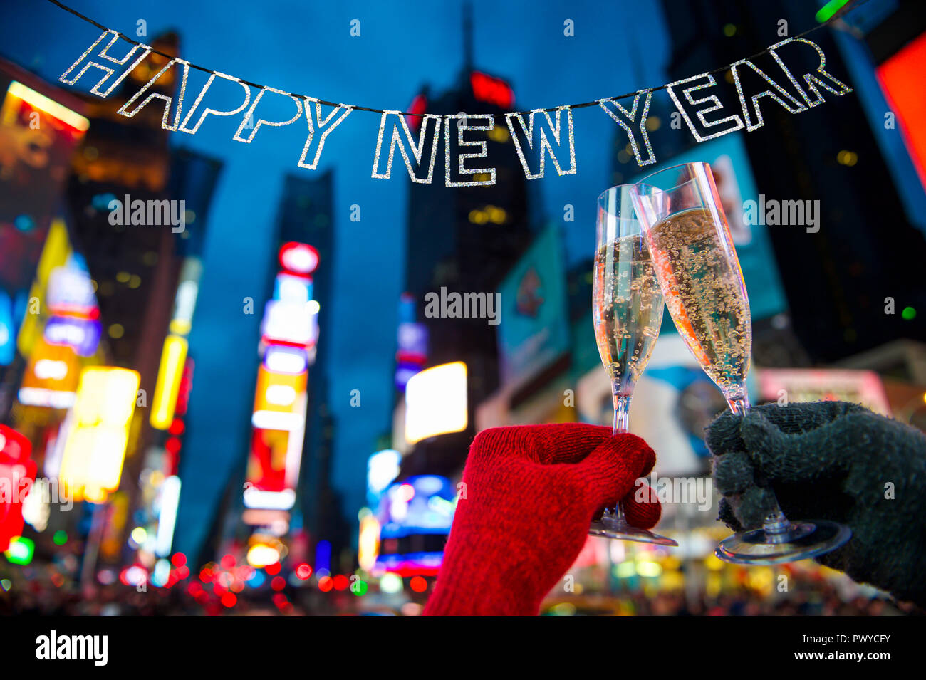 happy new year glitter bunting hangs in celebration over bright neon lights of times square in new york city usa
