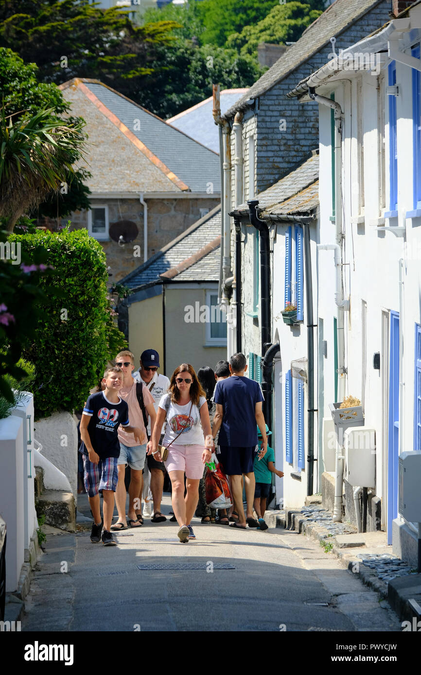 Holidaymakers on one of St Ives' narrow streets - Stock Image