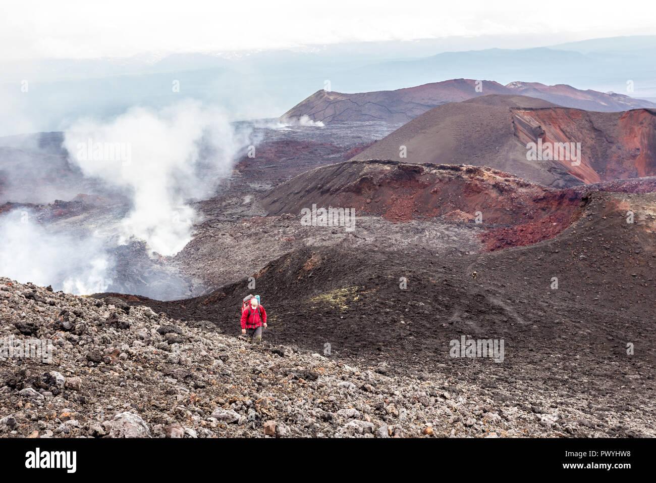 Petropavlovsk-Kamchatsky region, Russia - August 11, 2013: Tourist walking on a lava field near Tolbachik Volcano. - Stock Image
