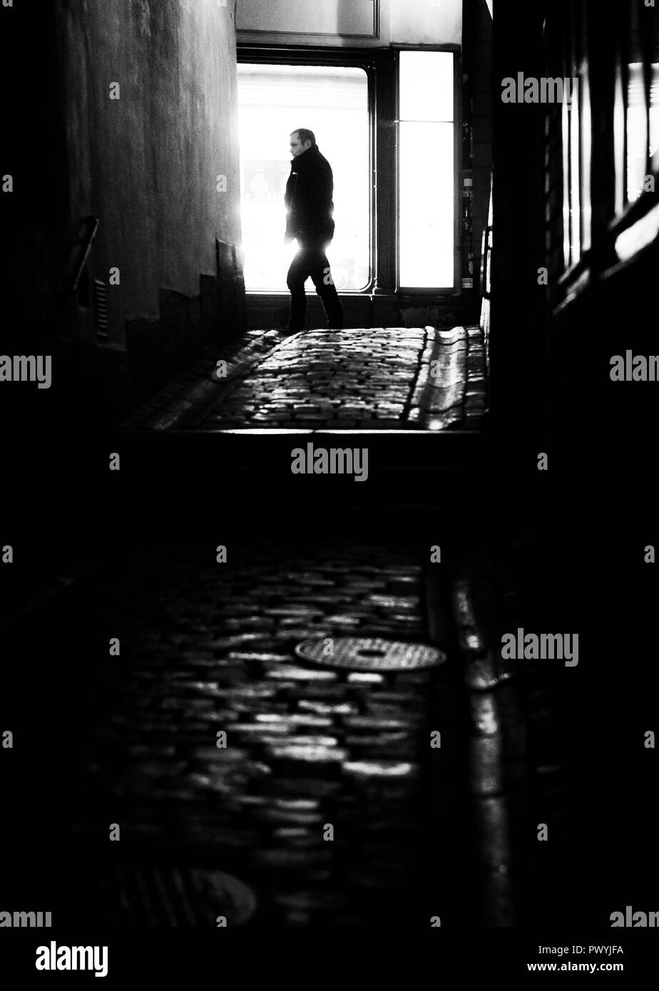 Silhouette of a man walking in an alley at night, Stockholm Sweden - Stock Image