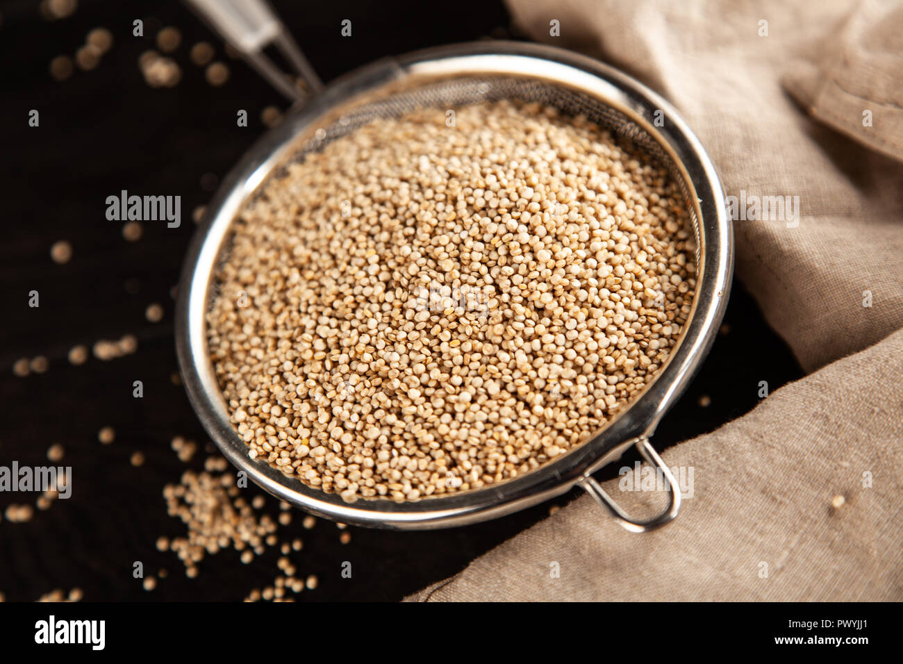 Raw quinoa seeds in a glass jar - Stock Image