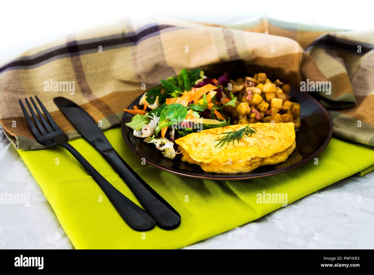 French Omelette with Potatoes, Mushroom and Salad - Stock Image