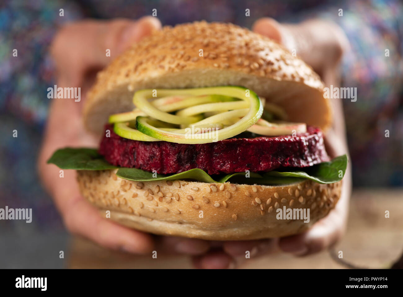 closeup of a young caucasian man with a beet burger sandwich in his hands Stock Photo