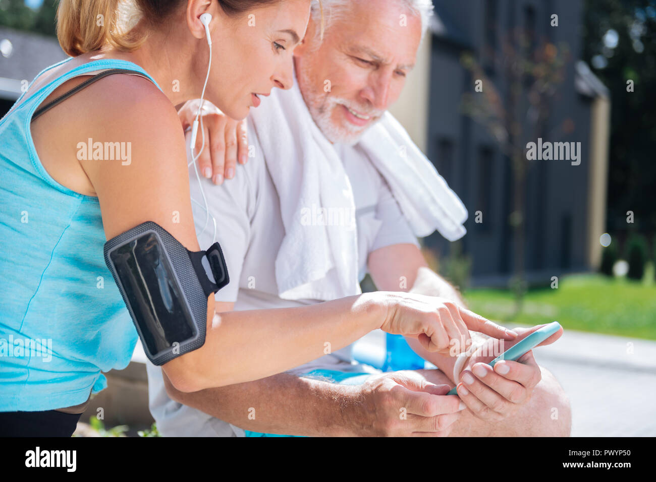 Couple of managers of world company checking work e-mail on phone together Stock Photo