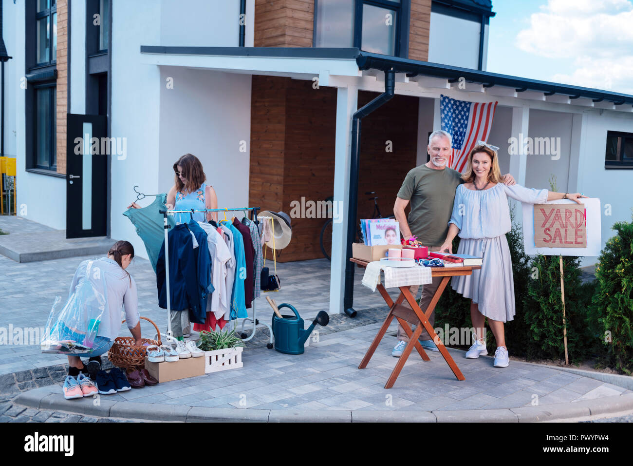 Generous and kind-hearted husband and wife feeling contended during yard sale - Stock Image