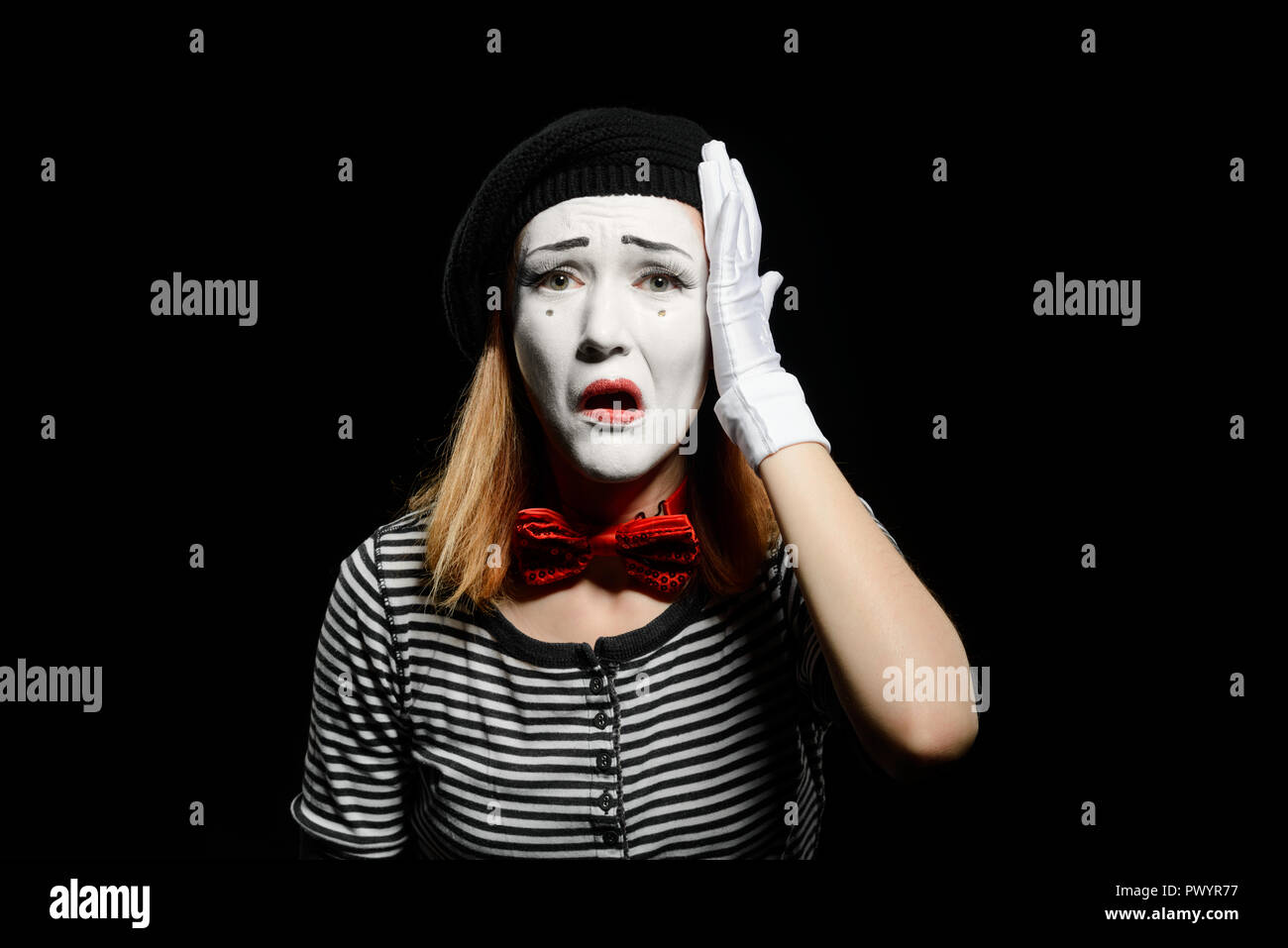 Upset female mime on black - Stock Image