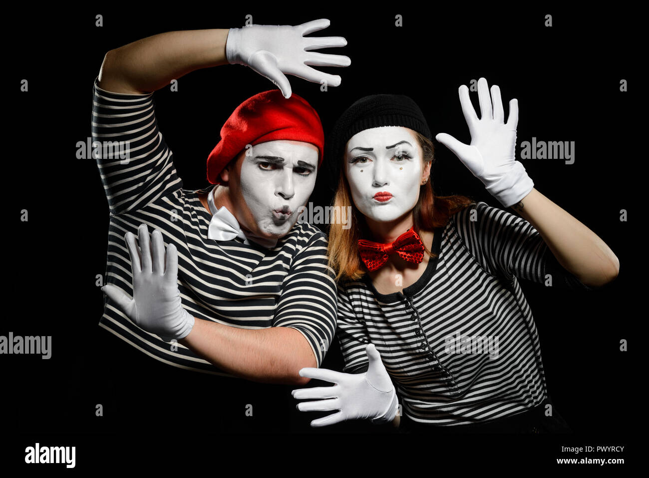Funny mime artists on black - Stock Image