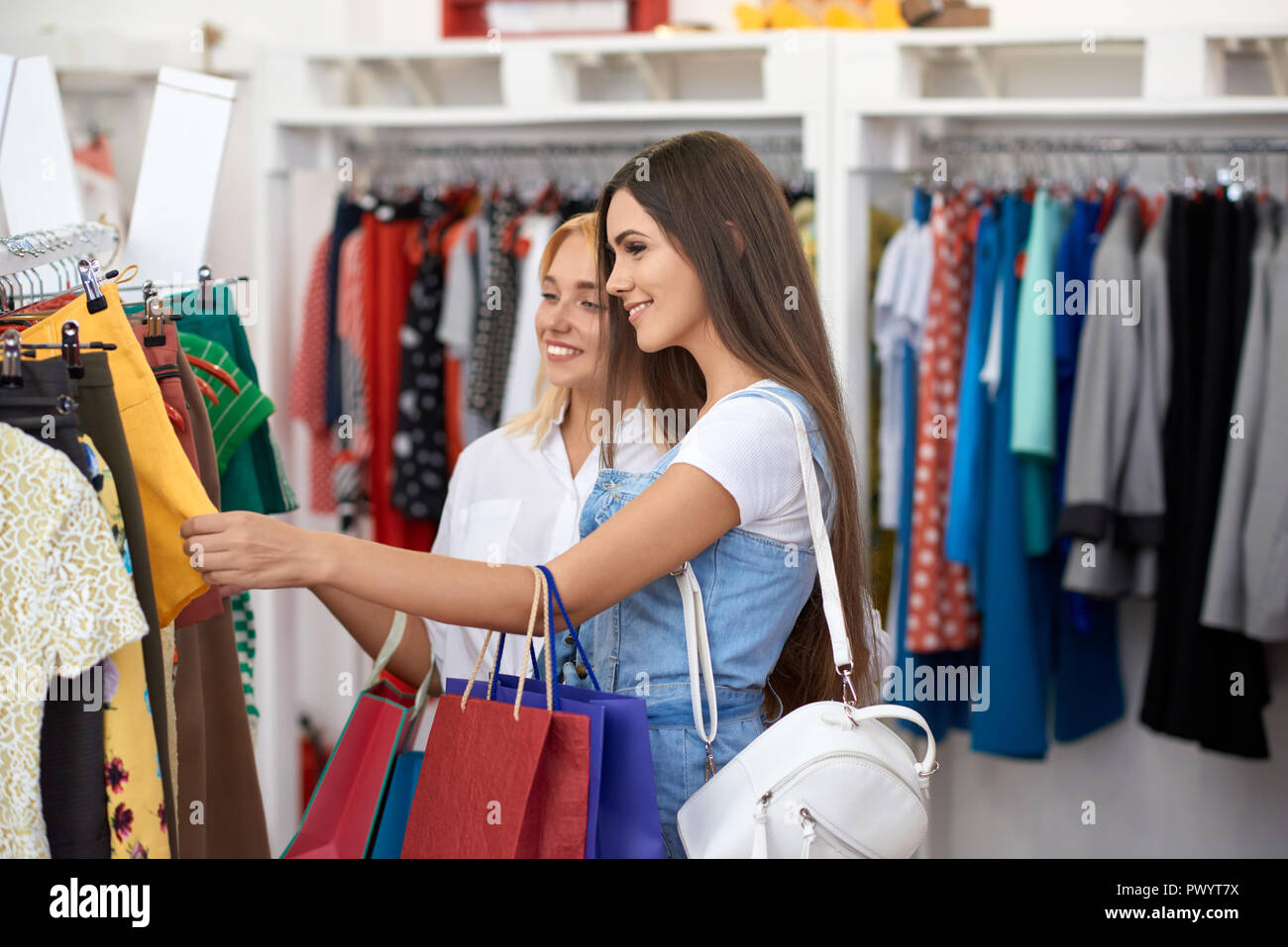 Side view of two pretty women choosing new clothes in mall. Smiling customers looking at shirts and skirts, discussing it and enjoying shopping process. Concept  of buying and happiness. - Stock Image