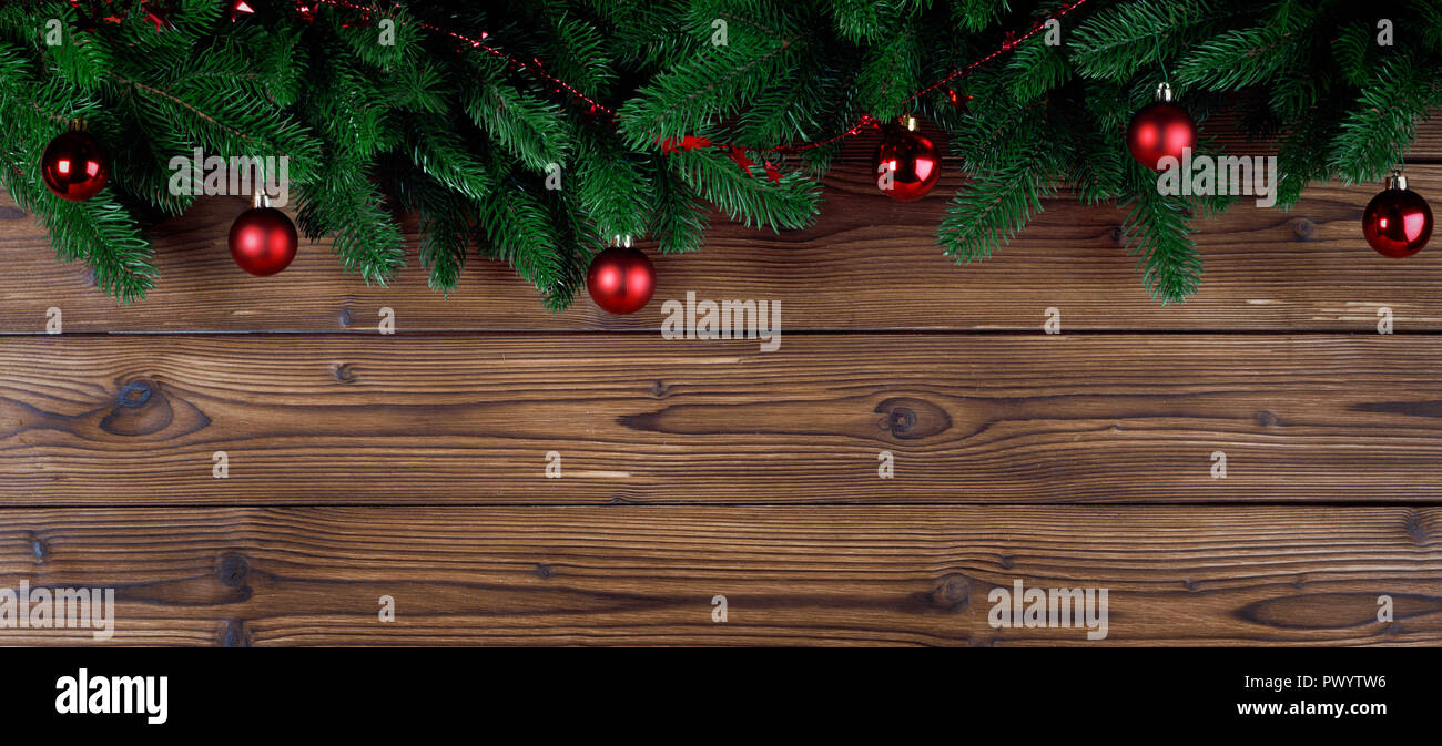 christmas tree decoration frame on wooden background fir tree branch red baubles copy space for text