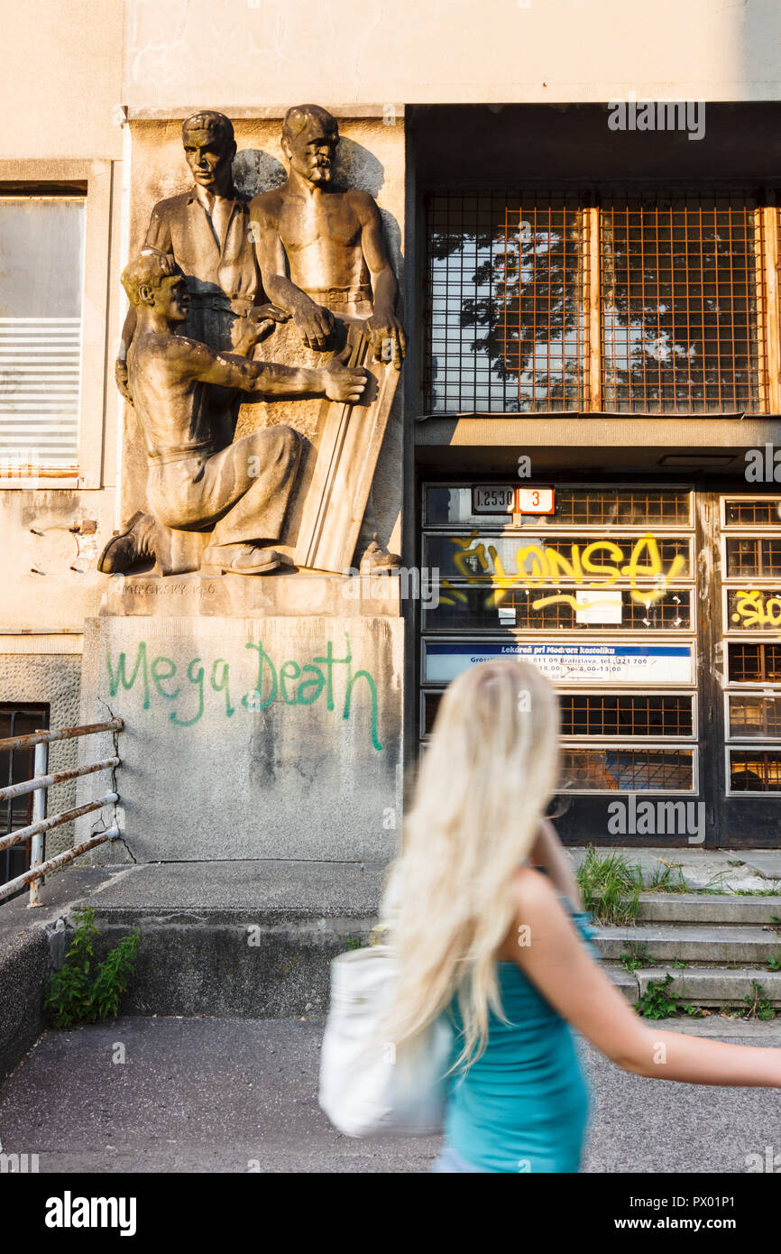 Blonde young woman walking past old communist-realist statues in Bratislava, Slovakia - Stock Image