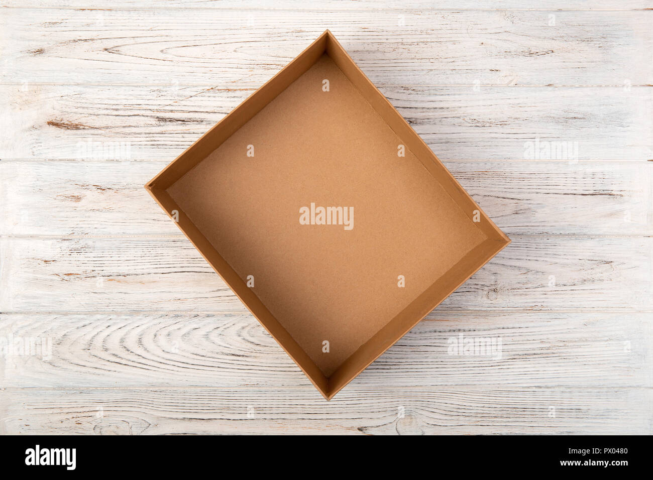 Empty Cardboard box on a white wooden background top view. - Stock Image