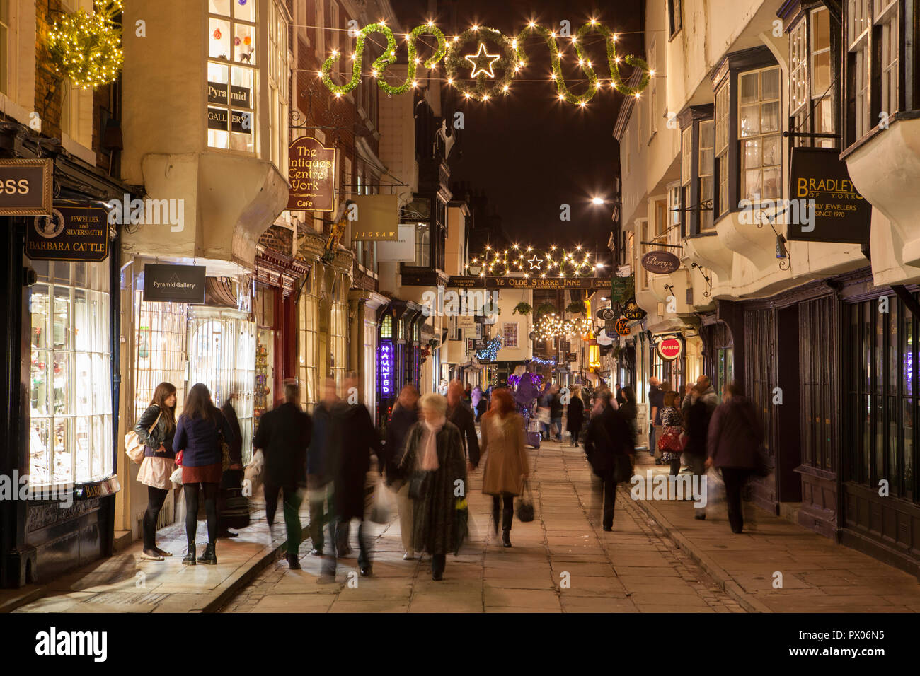 Night time photo of Stonegate in York with Christmas shoppers - Stock Image
