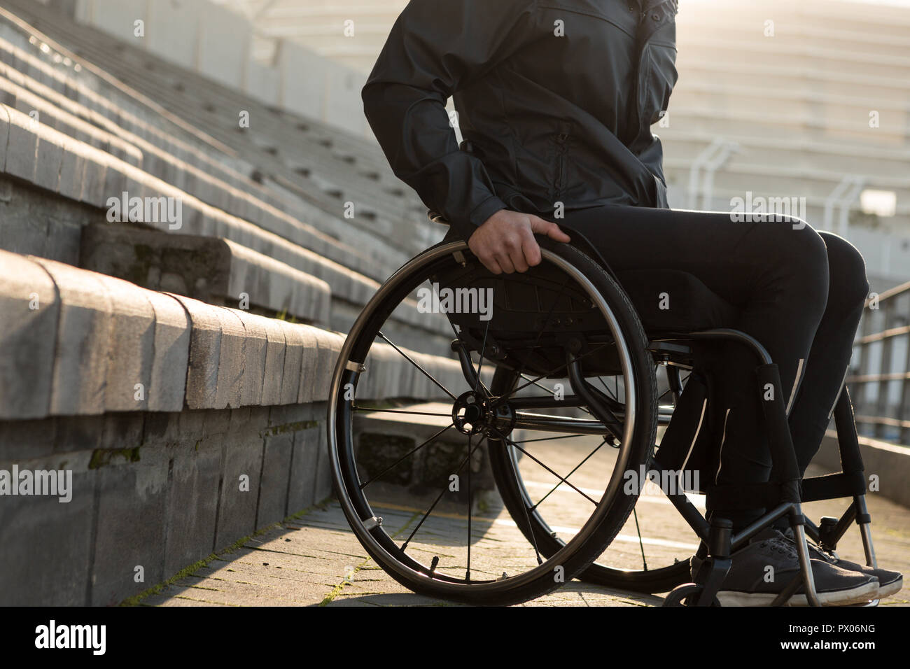 Disabled athletic moving with wheelchair at sports venue - Stock Image