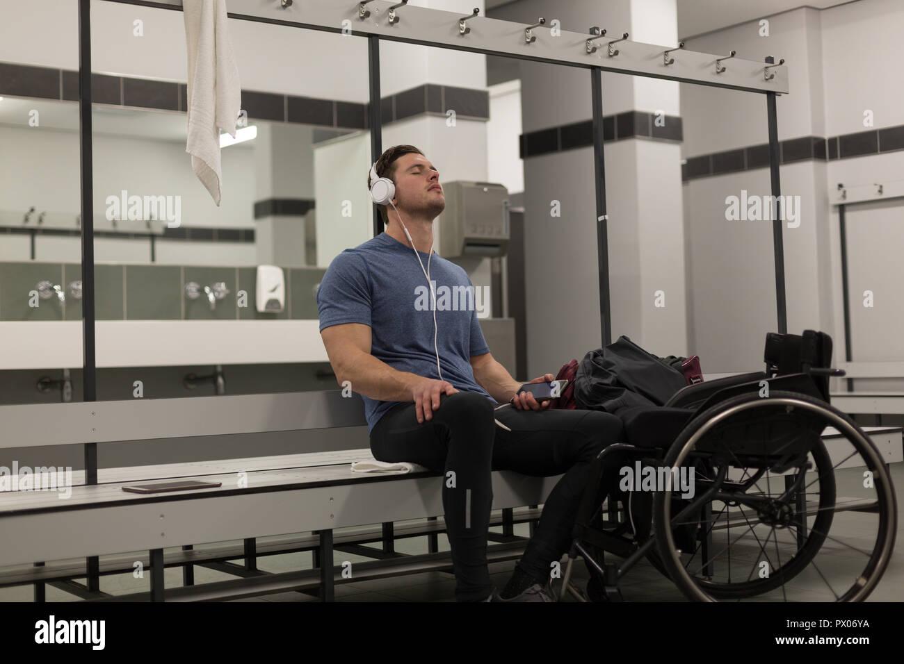 Disabled man listening music on headphones - Stock Image