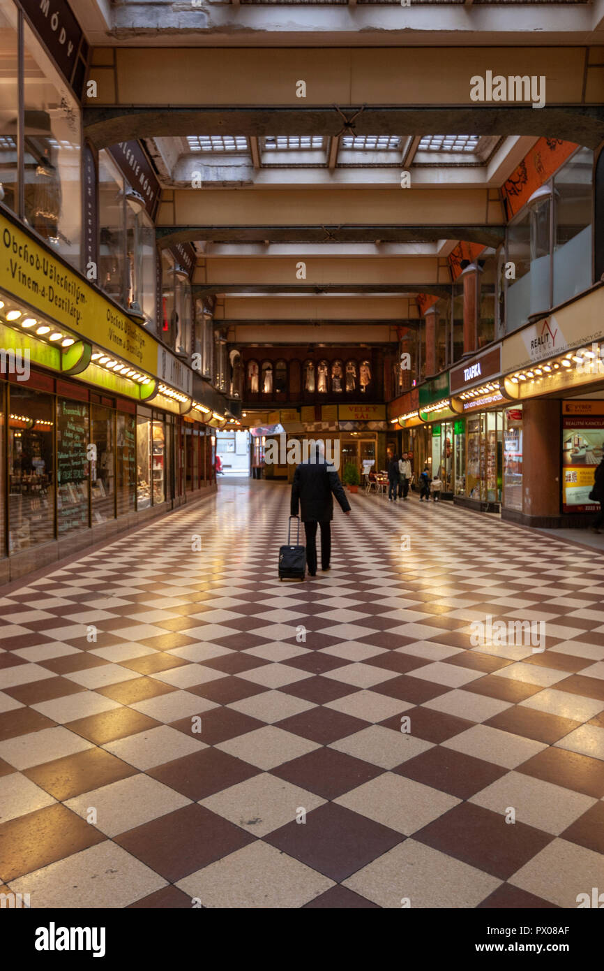 Man with a trolley baggage in the Lucerna Palace galleria, Prague, Czech Republic. - Stock Image