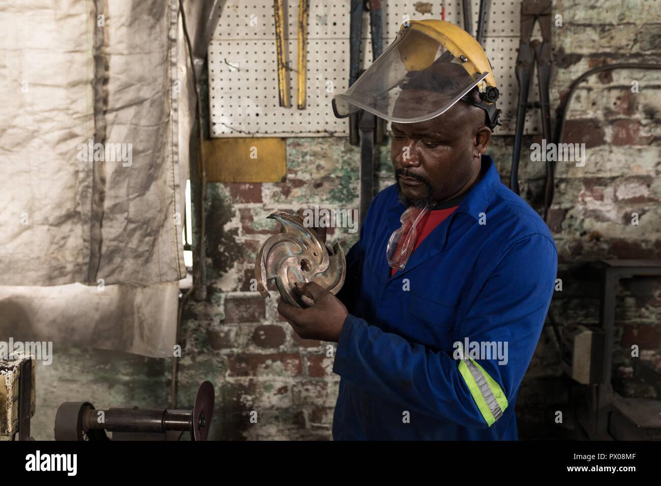 Blacksmith checking metal cutting blade in workshop - Stock Image