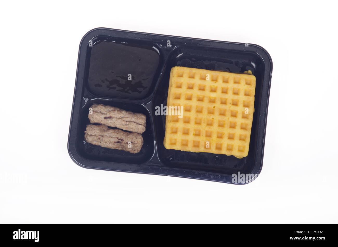 Microwave freezer breakfast meal of waffles with syrup and sausages - Stock Image