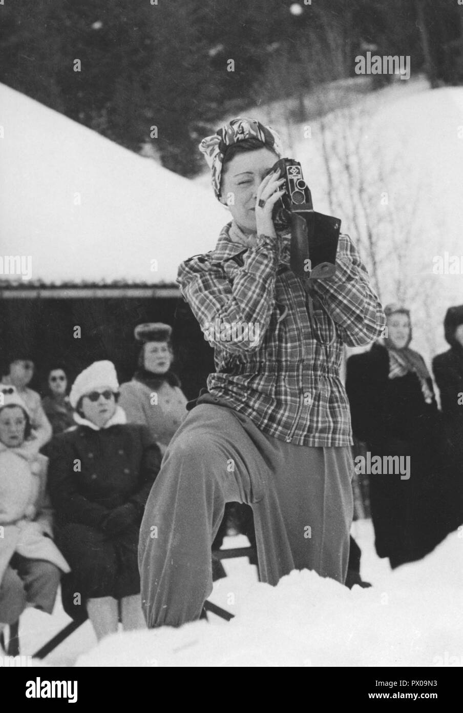 Winter in the 1940s. A young woman is filming the curling championships happening in Åre Sweden. 1940s. - Stock Image