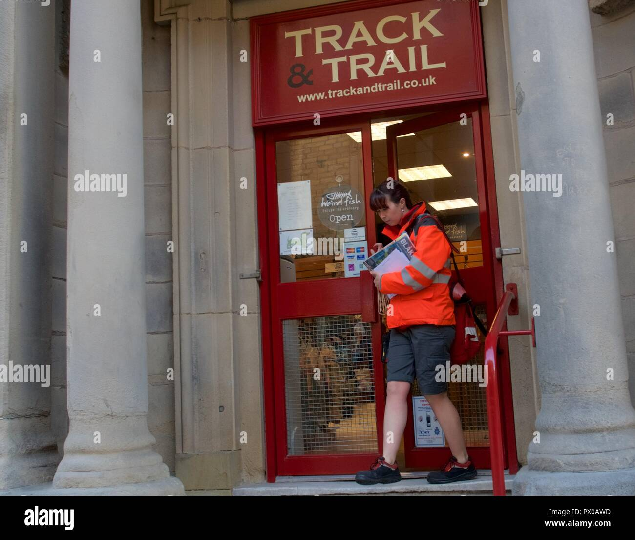 A postal worker leave a business after delivering mail.in Buxton, Derbyshire,  UK - Stock Image