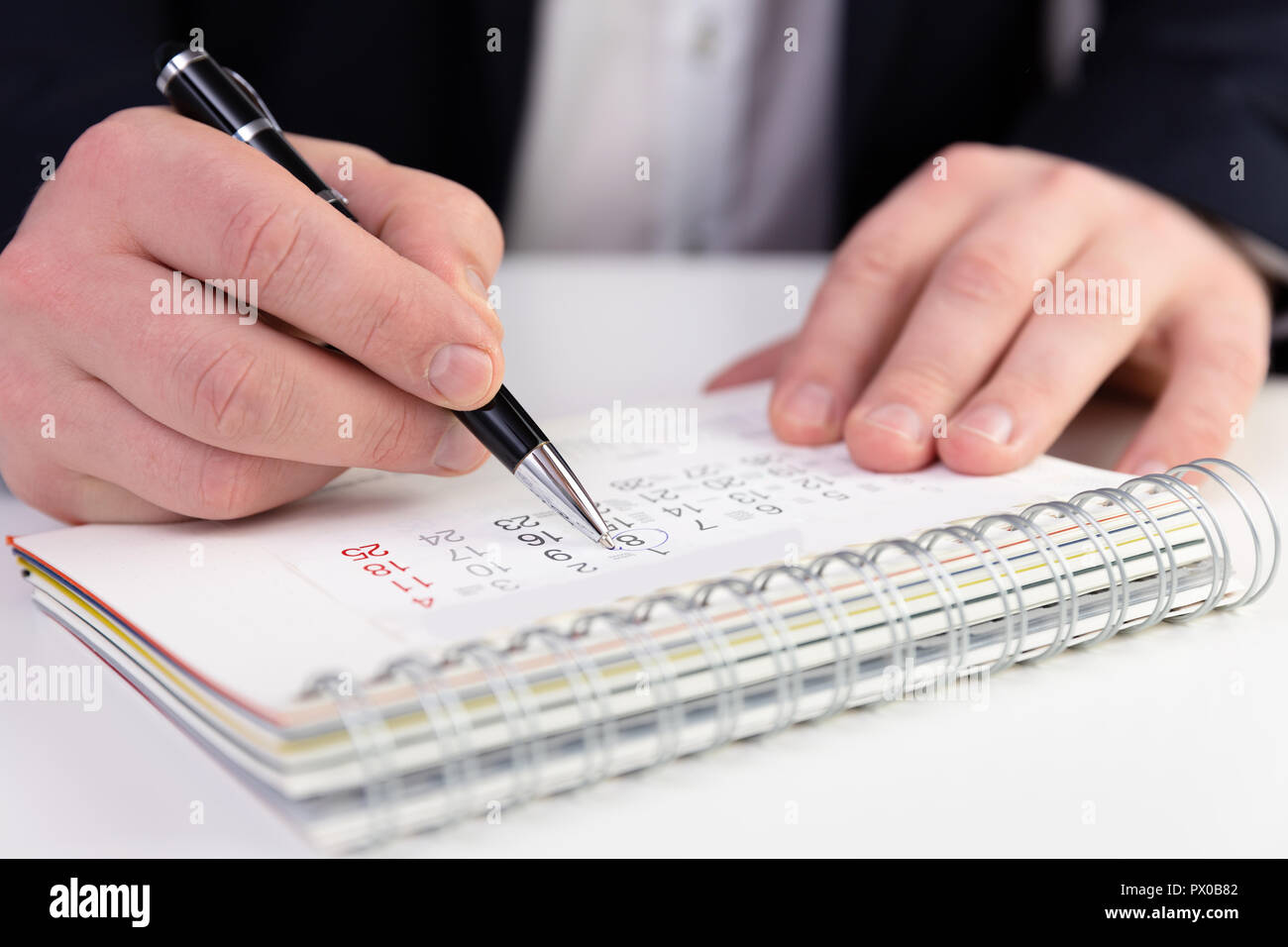 Business man marking a date on a calendar in a dark blue suit. - Stock Image