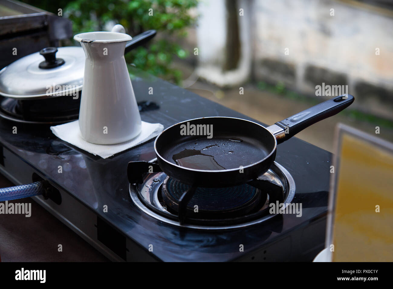 heating oil in stainless steel pan on gas fueled stove, prepared for frying breakfast or lunch food in an outdoor kitchen background. Kitchen Utensils - Stock Image