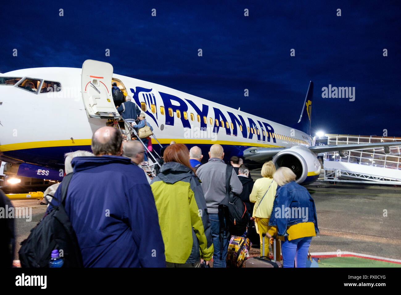 Passengers board a Ryanair aircraft for a flight from Glasgow Prestwick airport. - Stock Image