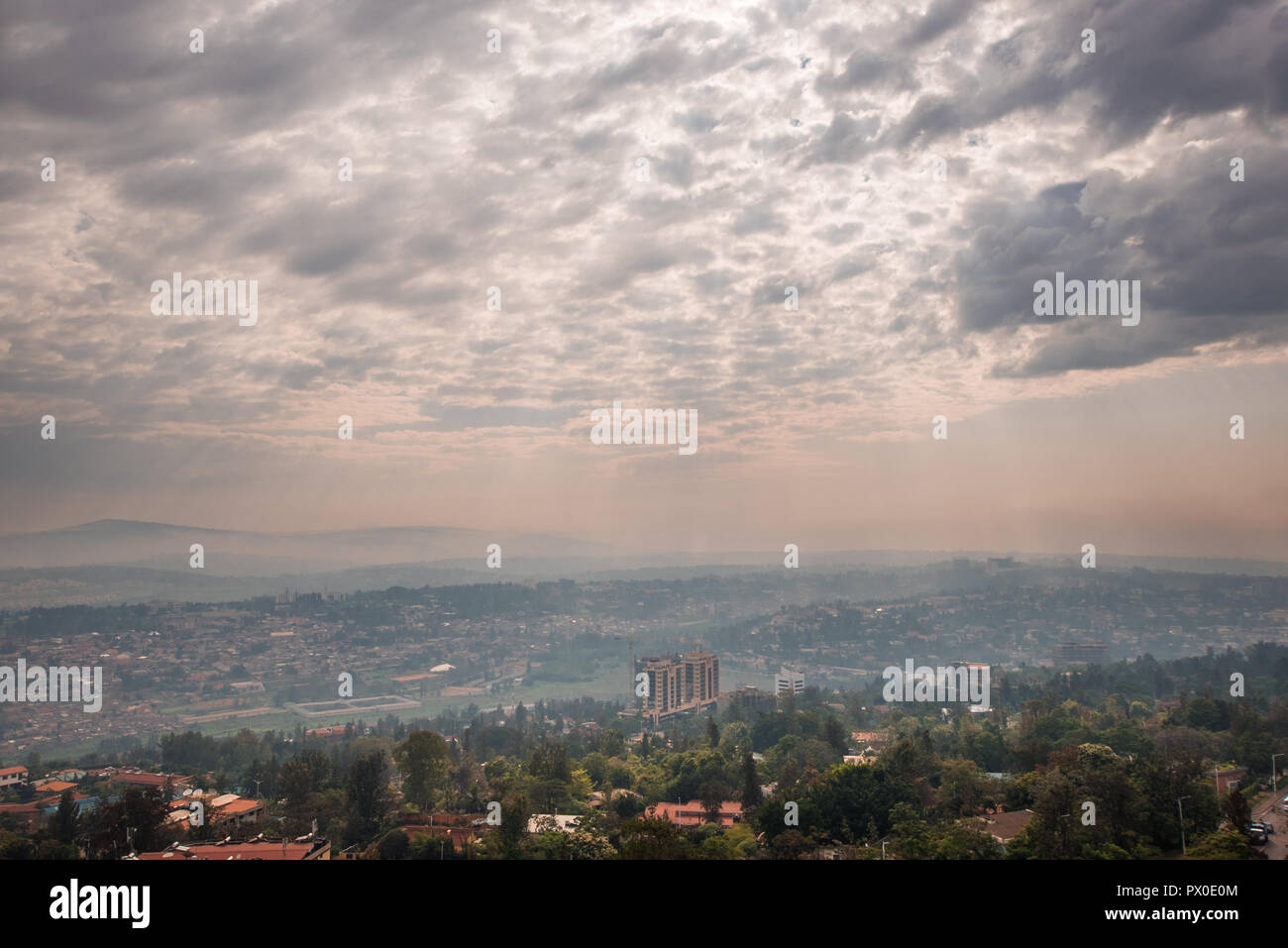 Sunlight breaks through the clouds over the hills of Rwanda that stretch into the distace - Stock Image