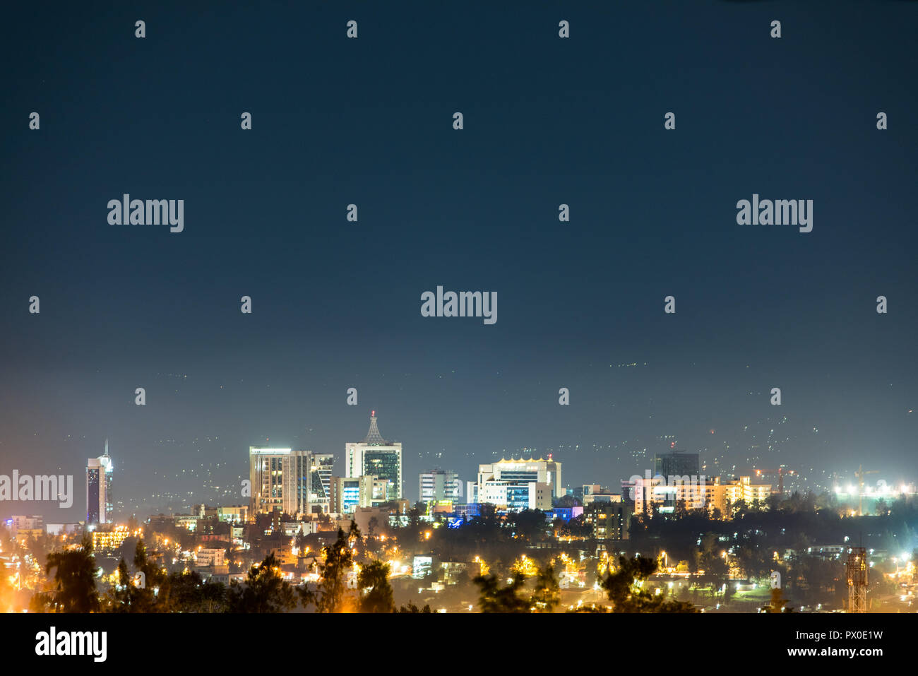 A wide view of Kigali city skyline lit up at night, under a deep blue evening sky - Stock Image