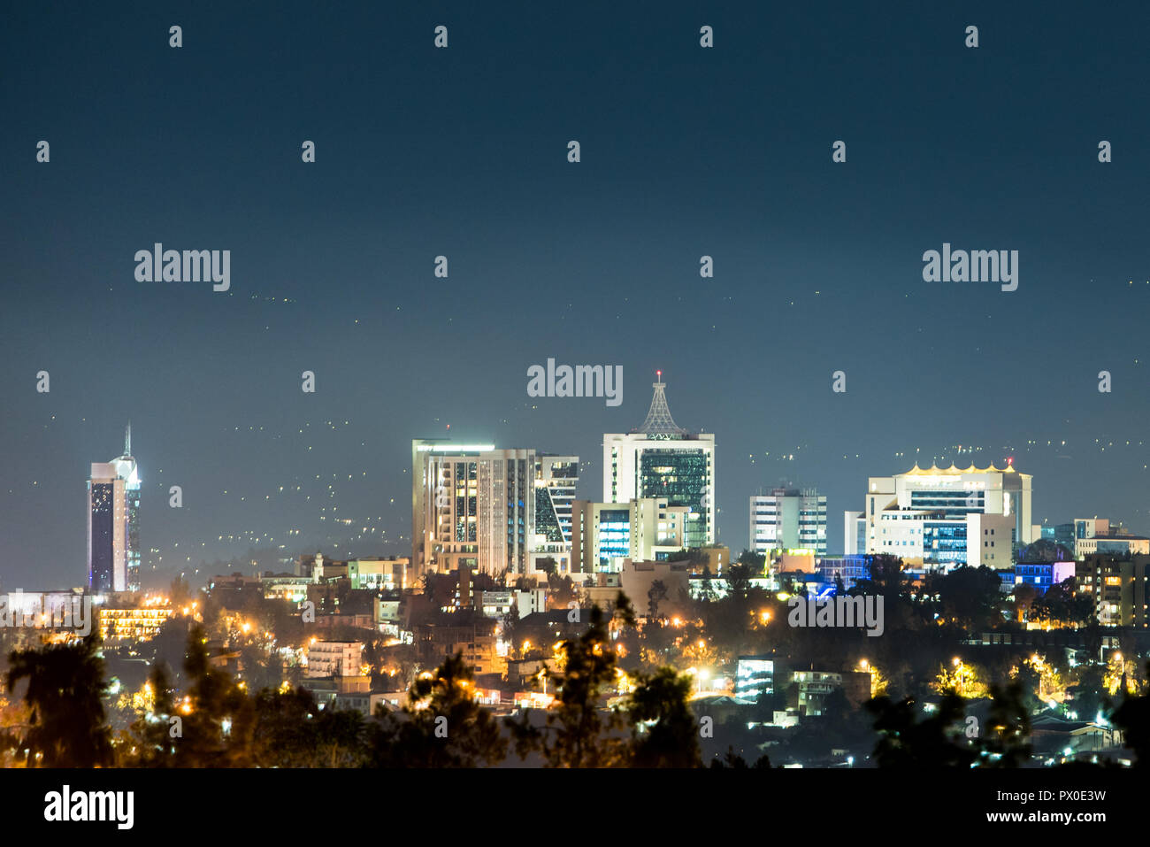 A closeup view of Kigali city skyline lit up at night, under a deep blue evening sky - Stock Image