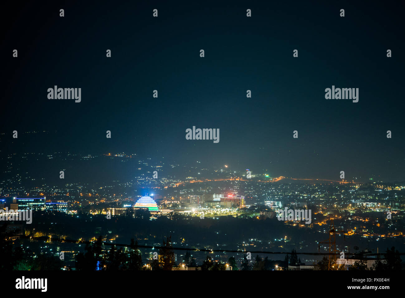 A wide view of city lights on the hills at night, with Kigali Convention Centre lit up in the colours of the Rwandan - Stock Image