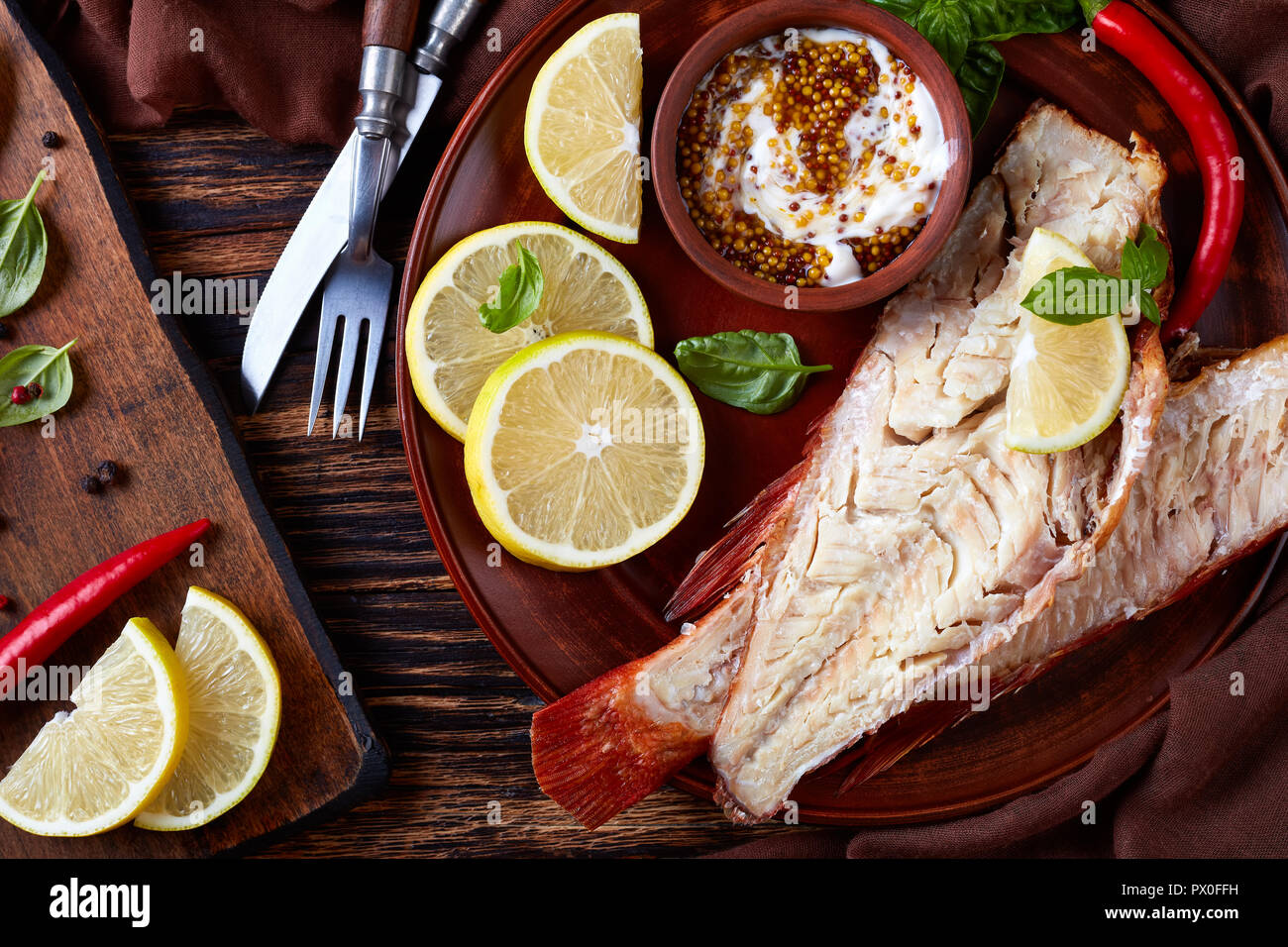 fillet of hot smoked red snapper served on a earthenware plate with fresh basil leaves, lemon slices and mustard sauce, fork and knife on a wooden rus Stock Photo