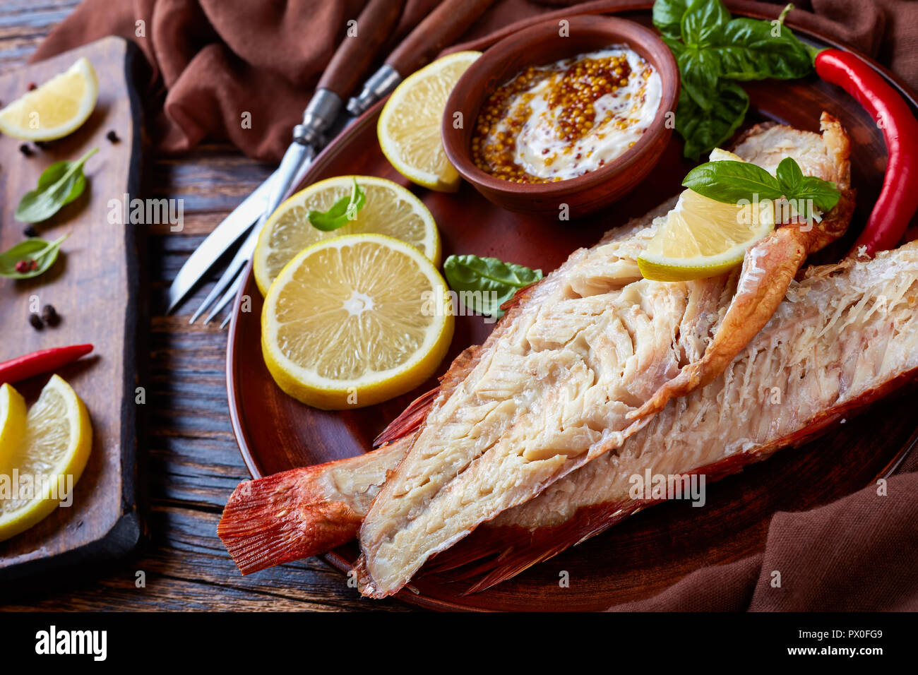 fillet of  red snapper served on a earthenware plate with fresh basil leaves, lemon slices and mustard sauce, fork and knife on a wooden rustic table, Stock Photo