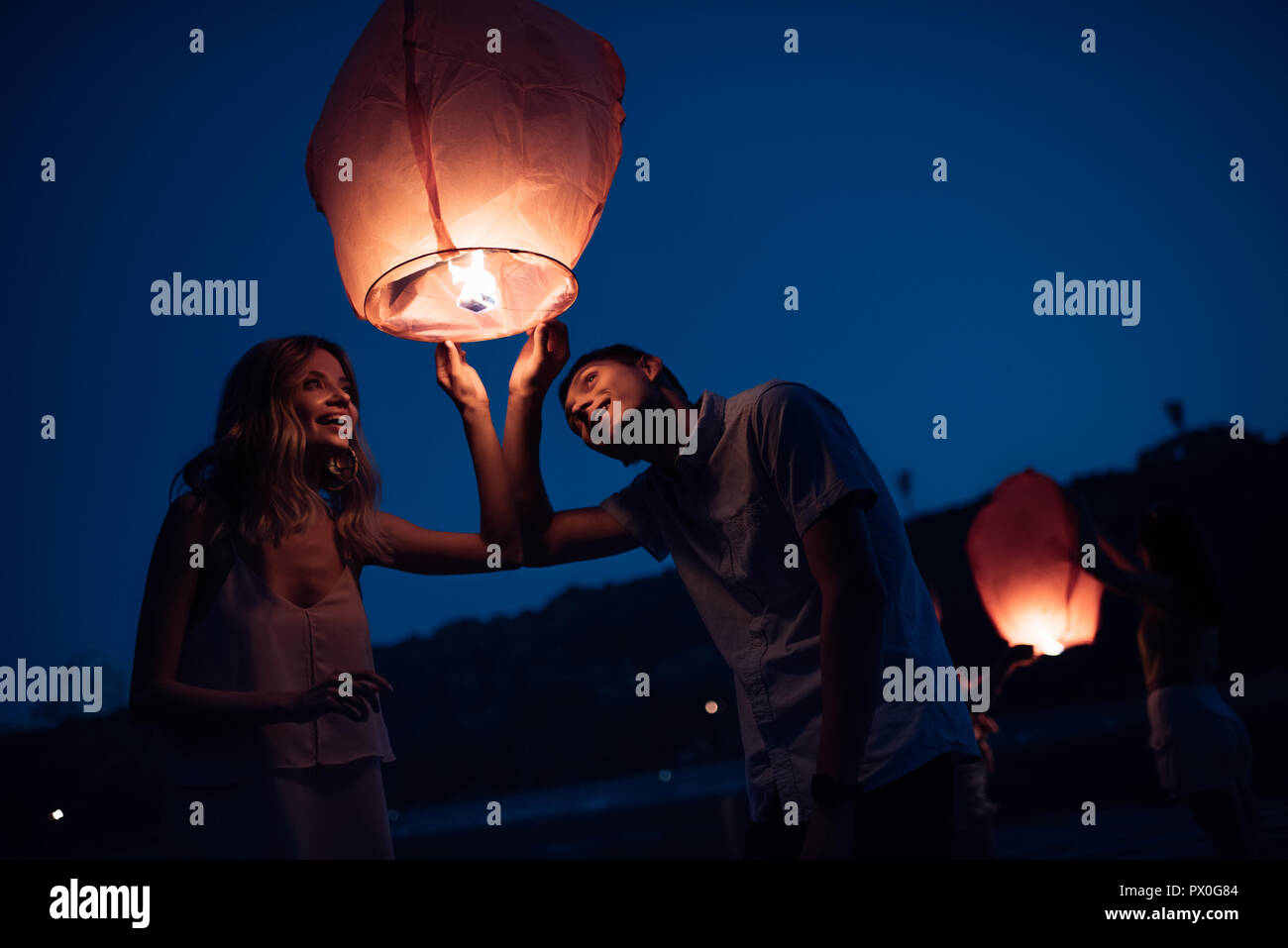 Young Couple Looking At Sky Lantern On River Beach In Evening Stock Photo Alamy