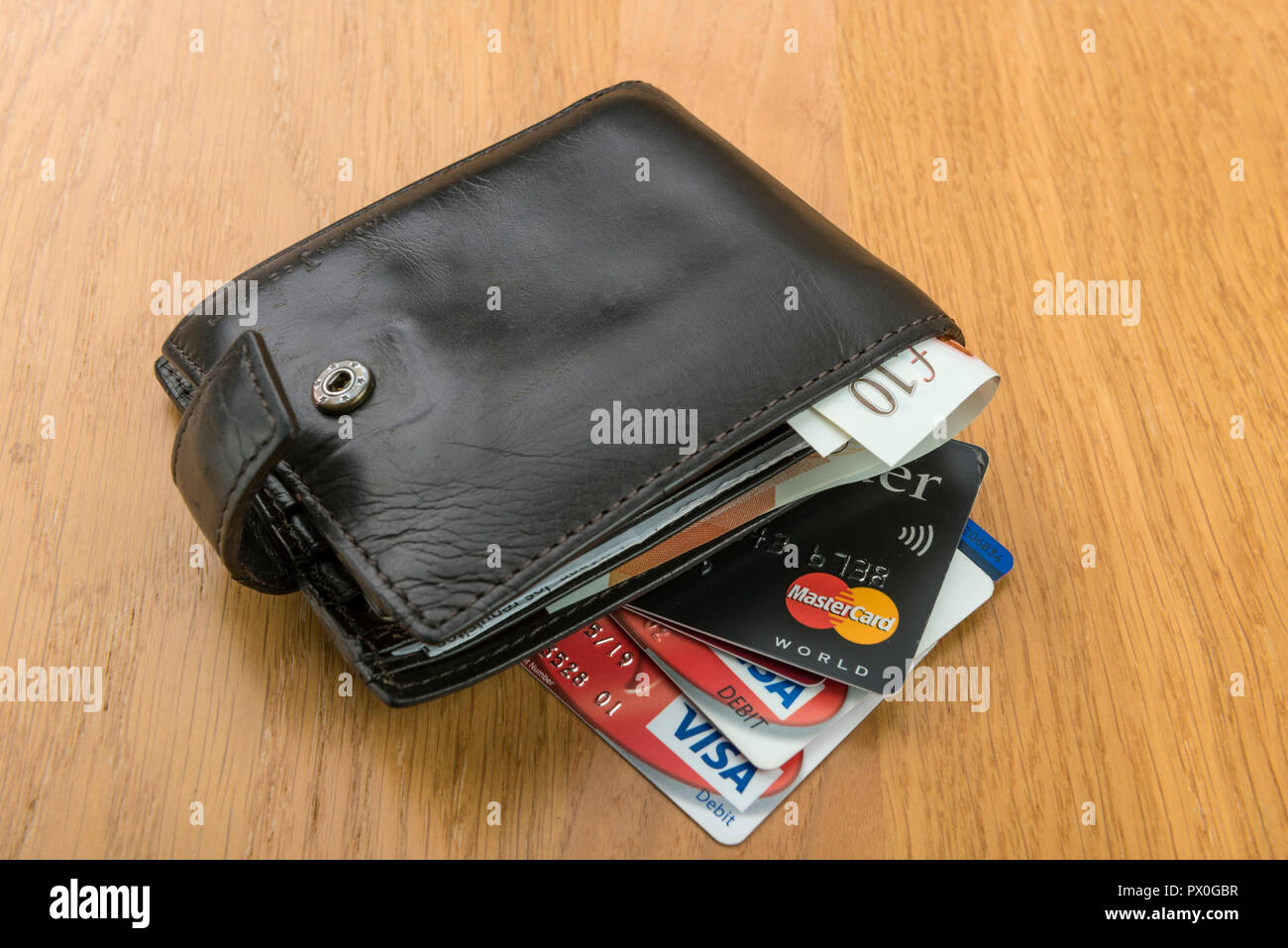 Mans old leather wallet with credit cards and pound sterling banknotes. - Stock Image
