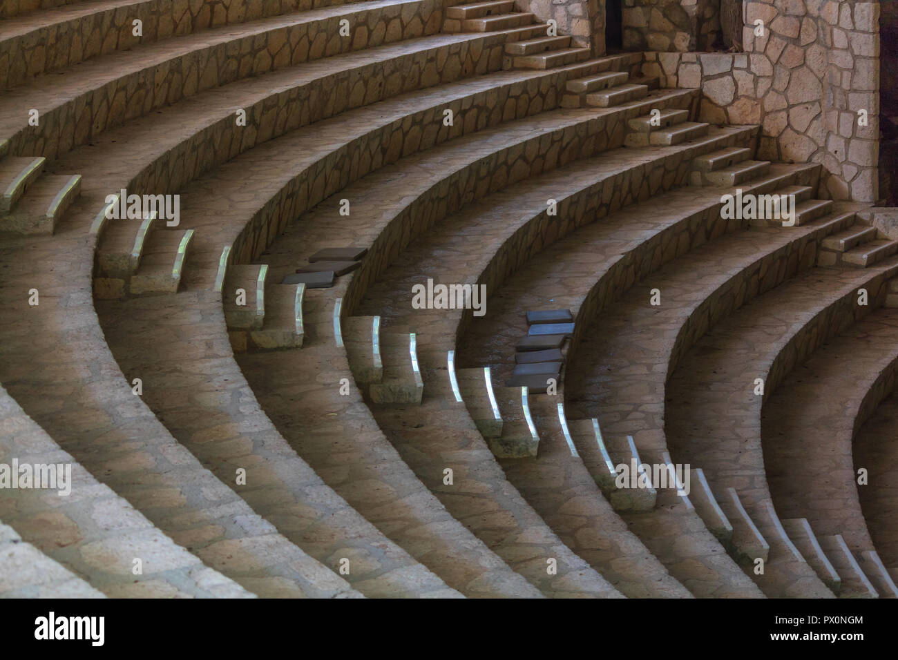 Empty amphitheater steps made of white stone. There is harmony in empty buildings. the parallel curves please the eye and bring peace to OCD people Stock Photo