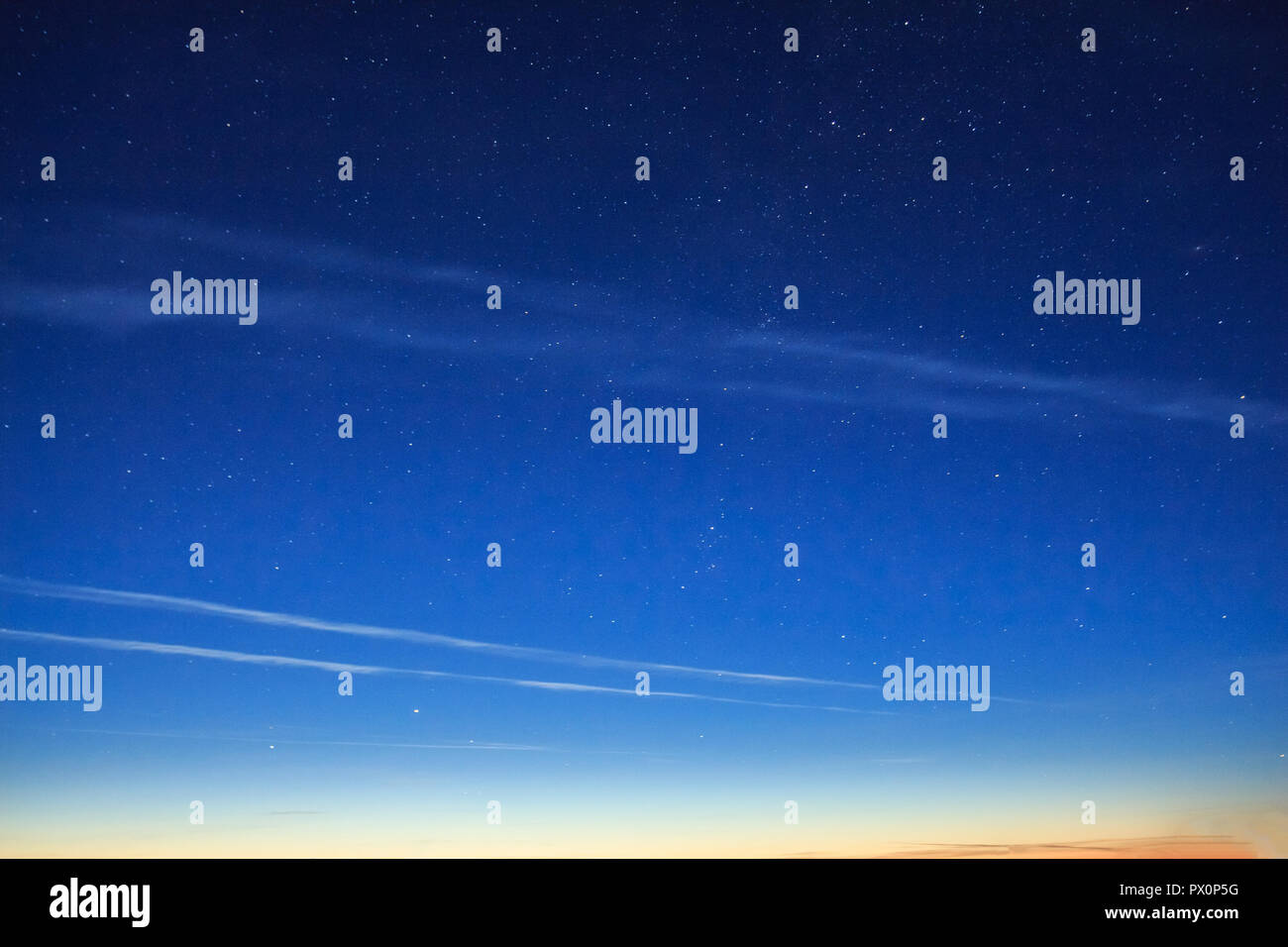 Stars in the sky before dawn with rare silvery clouds - Stock Image