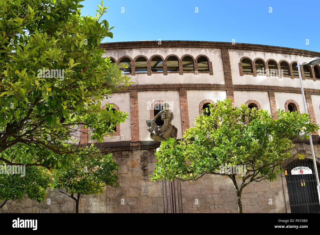 Bullring with torero statue and trees with green leaves. Public park, sunny day, blue sky. Pontevedra, Spain. Stock Photo