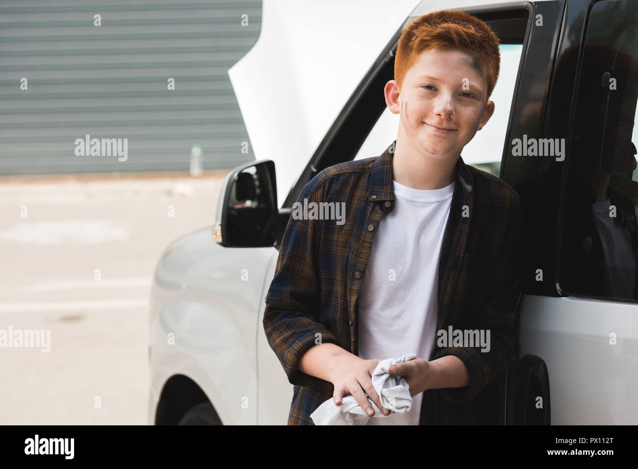 cheerful red hair preteen boy looking at camera after repairing car - Stock Image