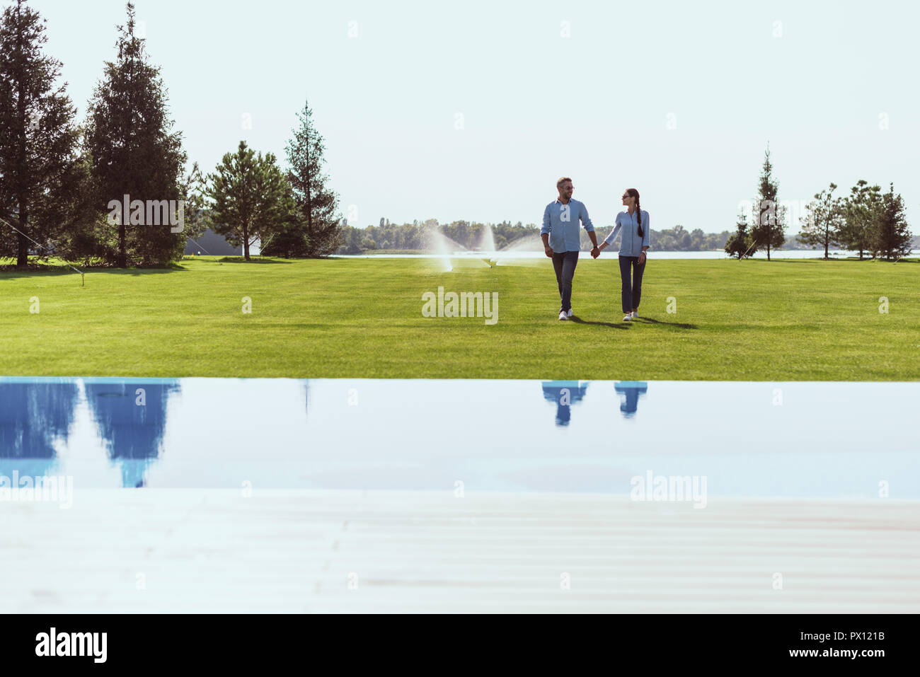 couple holding hands and walking on green lawn near swimming pool at country house - Stock Image