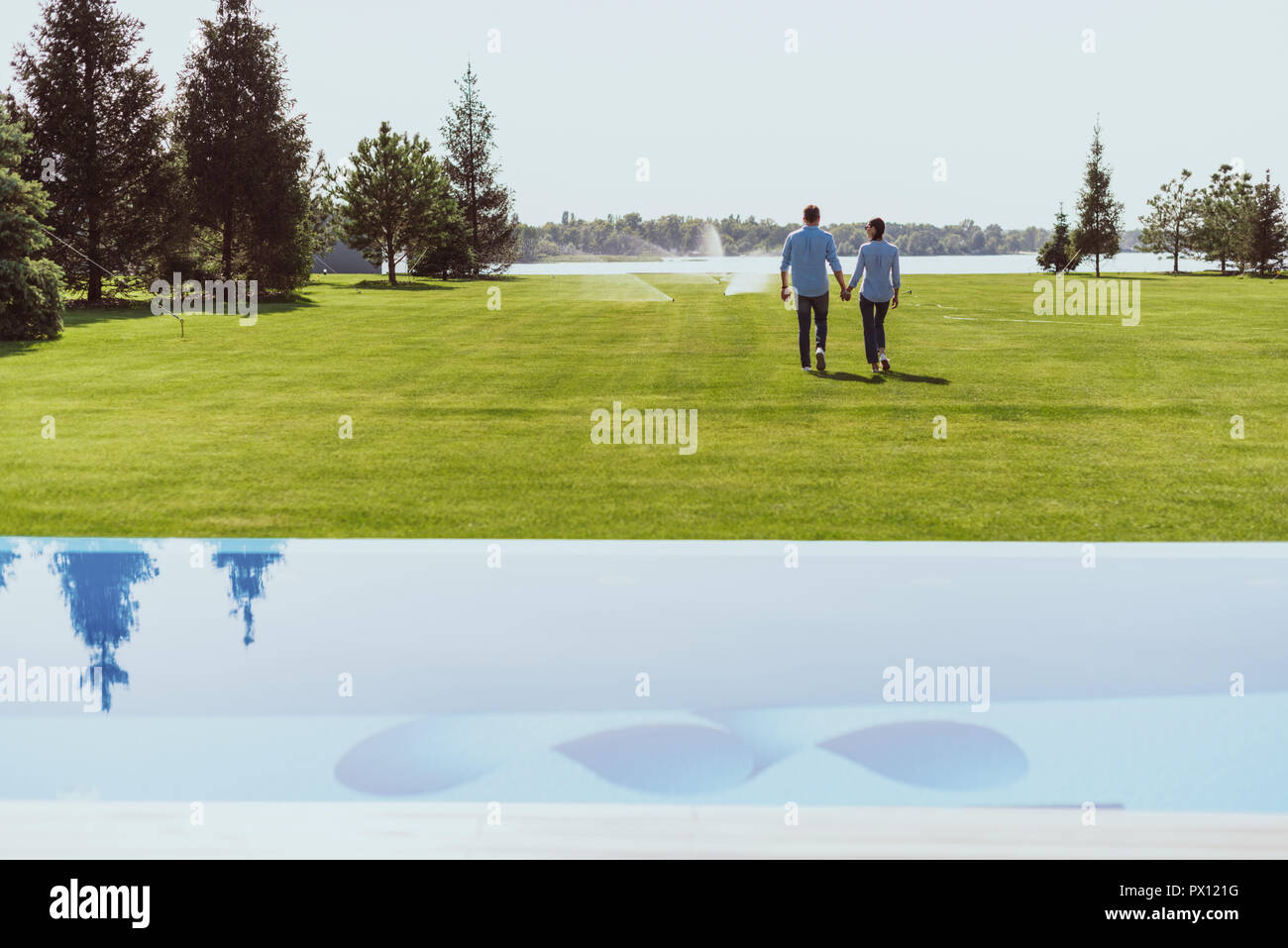 rear view of couple holding hands and walking on green lawn near swimming pool at country house - Stock Image