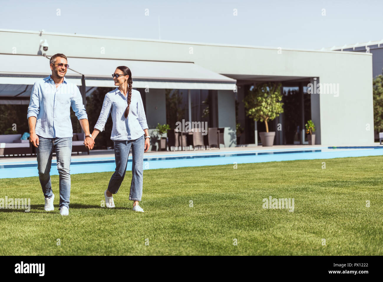 smiling couple holding hands and walking on green lawn near swimming pool at country house - Stock Image